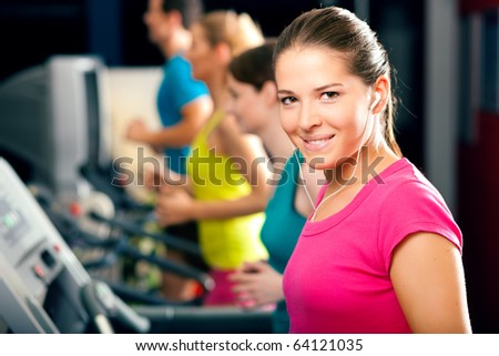 Running on treadmill in gym - group of women and men exercising to gain more fitness - stock photo