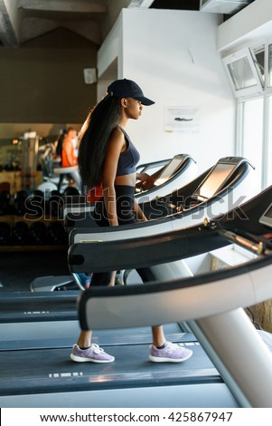Running on treadmill in gym or fitness club - sexy black woman exercising to gain more fit - stock photo