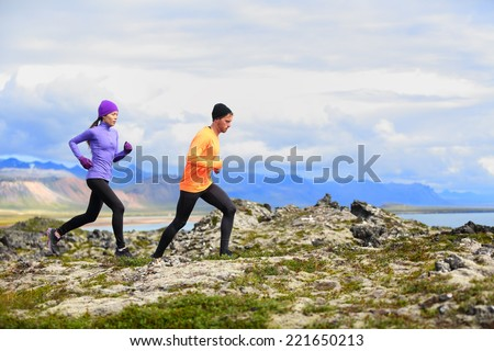 Running people trail runners in cross country run. Woman and man runners training jogging outdoors in beautiful mountain nature landscape on Snaefellsnes, Iceland. - stock photo
