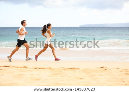 Running people - woman and man athlete runners jogging in sand on beach. Fit young fitness couple exercising healthy lifestyle outdoors. Male athlete and female fitness model training together. - stock photo