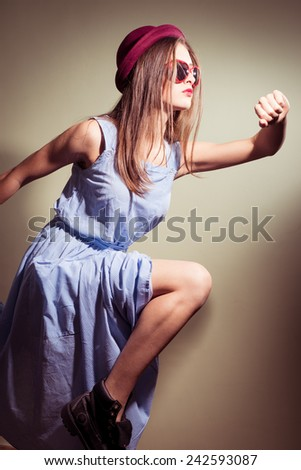 running pretty girl with glasses in the shape of hearts and blue dress - stock photo