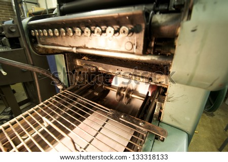 Running printing press with printed pages coming down the line. - stock photo