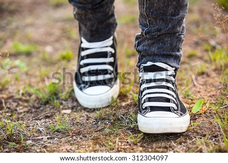 Running rubber shoes are on the legs, person walking on earth - stock photo
