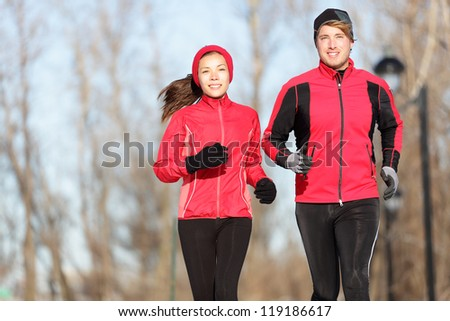 Running. Runners jogging outside. Young couple training outside in warm sport clothing outfit. Beautiful young interracial couple, Asian woman and Cauasian man. - stock photo