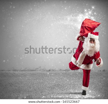 Running Santa Claus with sack full of magic gifts - stock photo