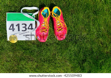 Running shoes and marathon race bib (number) on grass background, sport, fitness and healthy lifestyle concept  - stock photo