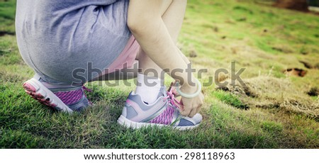 Running shoes. Barefoot running shoes closeup. Female athlete tying laces for jogging on road in minimalistic barefoot running shoes. Runner getting ready for training. Sport lifestyle - stock photo