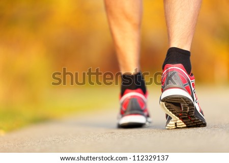 Running shoes closeup. Runner on road in fall autumn colors - closeup of male running walking shoes of jogger outdoors. - stock photo