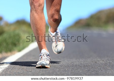 Running shoes - runner legs and running shoe closeup of man jogging outdoors on road. - stock photo
