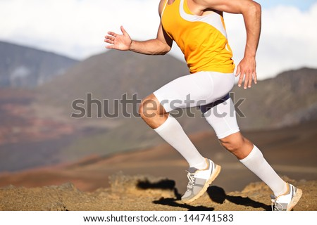 Running sport fitness man. Closeup of strong legs and shoes in action. Male athlete fitness runner sprinting fast outside in compression sports clothing, socks and tights shorts. Trail running concept - stock photo