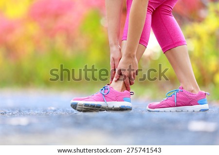 Running sport injury - twisted broken ankle. Female athlete runner touching foot in pain due to sprained ankle. - stock photo