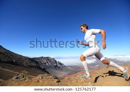 Running sport. Man runner sprinting outdoor in scenic nature. Fit muscular male athlete training trail running for marathon run. Sporty fit athletic man working out in compression clothing in sprint - stock photo