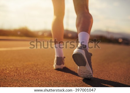 Running sport shoes on runner. Legs and running shoe closeup of man jogging outdoors on road.Selective focus - stock photo
