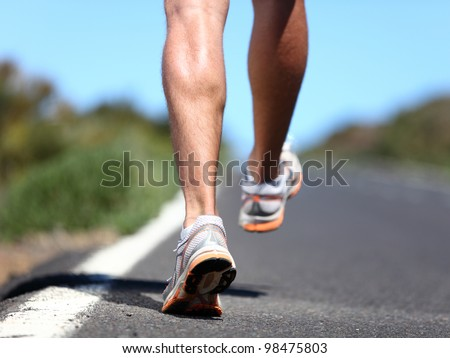 Running sport shoes on runner. Legs and running shoe closeup of man jogging outdoors on road. - stock photo