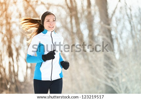 Running sport woman. Female runner jogging in cold winter forest wearing warm sporty running clothing and gloves. Beautiful fit Asian / Caucasian female fitness model. - stock photo
