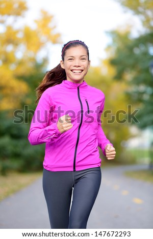 Running sport woman training in fall autumn forest or city park smiling happy. Asian female jogger working out outdoor energetic and fresh. Mixed race Asian Caucasian female fitness model. - stock photo