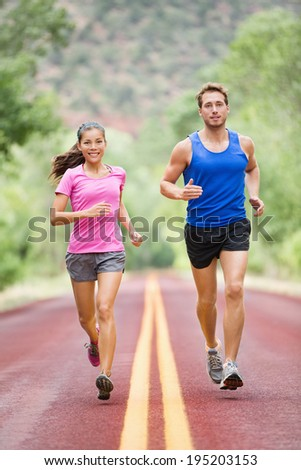 Running sporty people - two young runners jogging on road in nature training for marathon run. Multicultural couple, Asian woman sport model and man fitness model exercising together smiling happy - stock photo