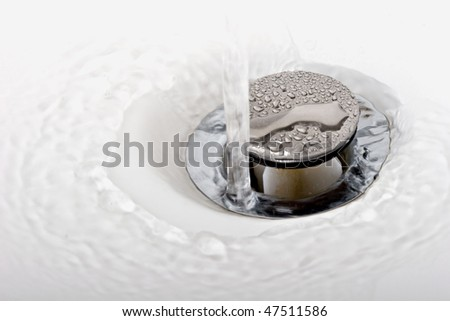 Running tap water in a sink down the drain - stock photo