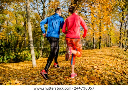 Running together - young couple jogging in autumn park, rear view - stock photo