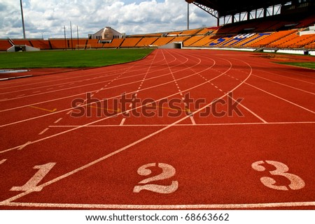 Running track numbers  in front of tracks and stadium with blue sky and white cloud. - stock photo