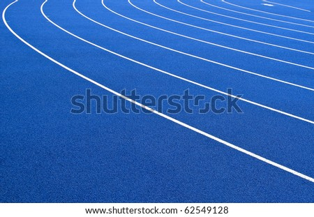 Running track with blue asphalt and white markings in outdoor stadium - stock photo