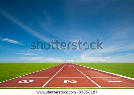 Running track with three lanes over sky and clouds - stock photo