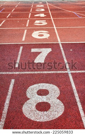 Running track with white lane numbers. - stock photo