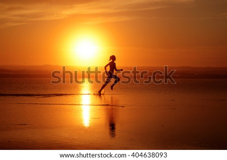 Running woman athlete silhouette at ocean line with sunset (full sun). With feet splashing water & track in the water - stock photo
