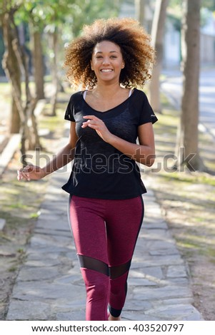 Running woman. Black Female Runner Jogging during Outdoor Workout in a Park. Beautiful fit Girl. Fitness model outdoors. Weight Loss - stock photo