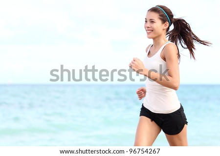 Running woman. Female runner jogging during outdoor workout on beach. Beautiful fit mixed race Fitness model outdoors. - stock photo
