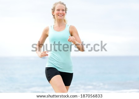 Running woman. Female runner jogging training outdoors on beach. Happy fit jogger living healthy lifestyle training outside. - stock photo