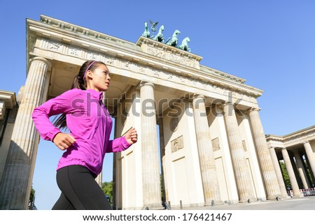 Running woman in Berlin, Germany by Brandenburg Gate jogging living healthy lifestyle. Female runner jogging. Urban fitness girl working out outdoors in jacket. - stock photo