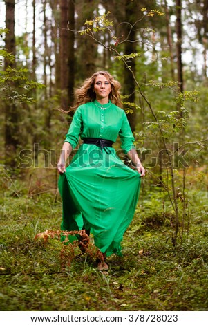 Running woman in long dress at forest. - stock photo