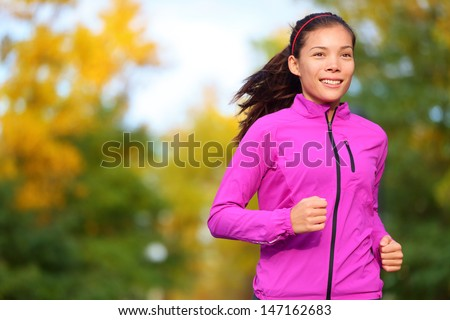Running woman jogging in autumn forest in fall. Beautiful female runner wearing autumn running jacket. Healthy lifestyle photo with beautiful mixed race ethnic Chinese Asian and Caucasian fitness girl - stock photo