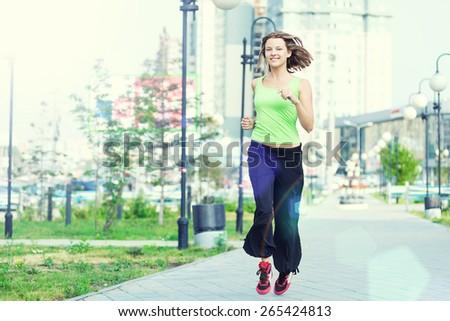 Running woman jogging in city street park at beautiful summer morning. Sport fitness model caucasian ethnicity training outdoor. - stock photo