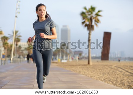 Running woman jogging on Barcelona Beach, Barceloneta. Healthy lifestyle girl runner training outside on boardwalk. Mixed race Asian Caucasian fitness woman working out outdoors in Catalonia, Spain. - stock photo