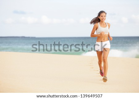 Running woman jogging on beach. Female runner training outside in summer. Fit young female sport fitness model exercising in full body. Beautiful fit Asian Caucasian woman in her twenties. - stock photo