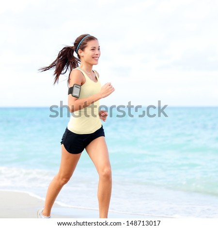 Running woman jogging on beach listening to music in earphones from smart phone mp3 player smartphone armband, Female runner training for marathon on beautiful beach. Mixed race Asian woman. - stock photo