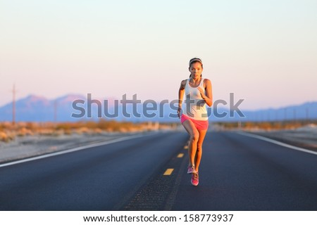 Running woman sprinting on road highway at sunset at countryside in USA. Fit female fitness girl training outdoor in beautiful landscape. Multiracial Caucasian Asian female runner in her 20s. - stock photo