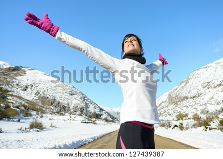 Running woman success bliss sport concept on winter road mountain background. Beautiful cheerful caucasian Female athlete with arms up. - stock photo