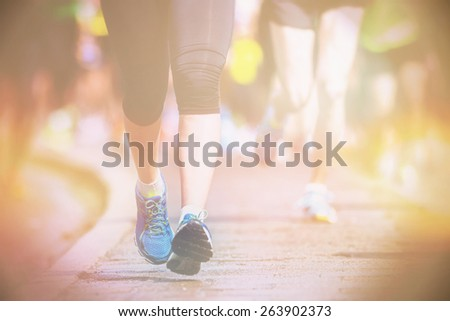 Running womans legs and feet closup during a marathon, filters applied - stock photo