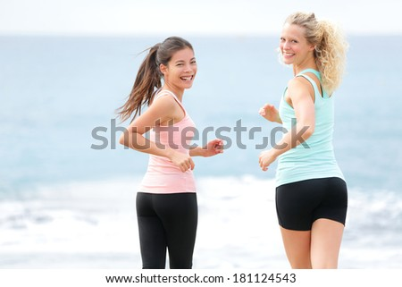 Running women jogging training on beach. Girlfriends runners exercising together smiling happy looking at camera. Two beautiful young woman in workout. Multiracial Asian and Caucasian. - stock photo