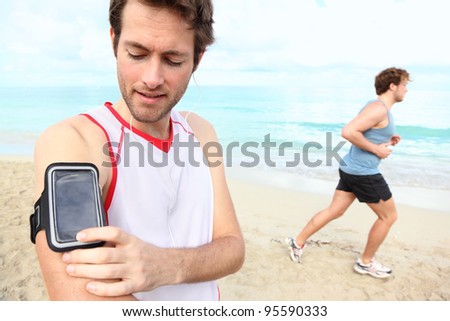 Running workout man with mp3 music player listening to music with mp3 player armband or smart mobile phone. - stock photo