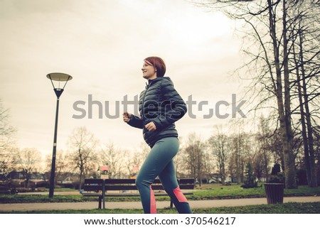 Running young girl jogging in a winter fleece  in a city park.Health and fitness concept - stock photo