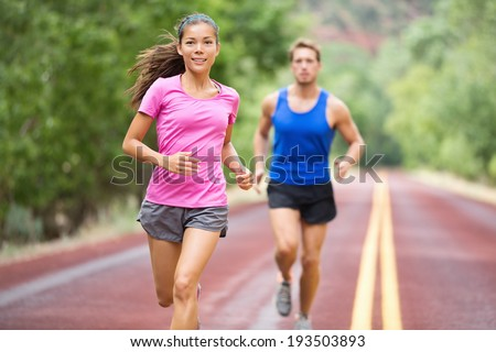 Running young mixed race couple training for marathon outside on road. Happy smiling beautiful mixed race female model in front - handsome caucasian male model blurred in background, running focused - stock photo