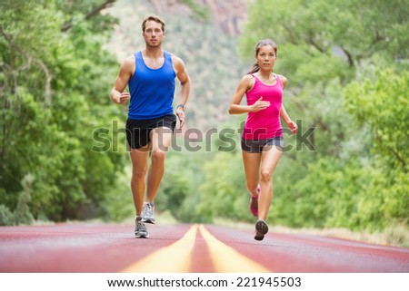 Running young people - two runners jogging on road in nature training for marathon run. Multicultural couple - asian mixed race beautiful model woman and caucasian male fitness model exercising - stock photo