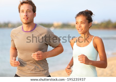 Running young pretty couple jogging on summer beach sand in sun. Exercising Caucasian fitness model and beautiful mixed race female sports model in 20s working out outdoors living healthy lifestyle. - stock photo