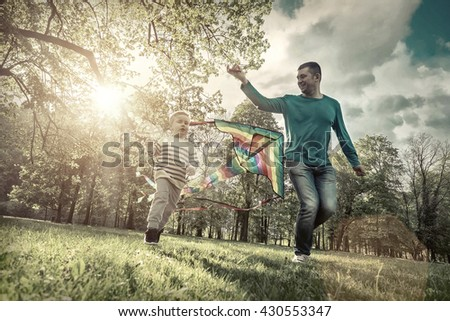 Runnings little boy and father flies with them kite in the park under sunligt. - stock photo