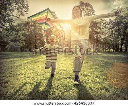 Runnings little boy and mother flies with them kite in the park under sunligt. - stock photo