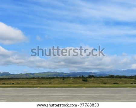 Runway of small airport shot against a backdrop of mountains and blue sky - stock photo